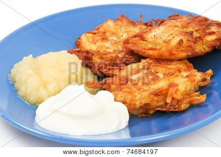 Traditional potato latkes or pancakes for Hanukkah with side of applesauce and sour cream