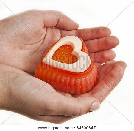 In the palms of the hands is a designer piece of orange soap in the form of heart. poster