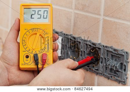 Electrician Hands With Multimeter Measuring The Voltage In A Wall Fixture