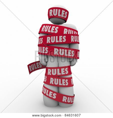 Rules word on red tape wrapped around a man or person to illustrate following regulations, guidance or laws to be in compliance