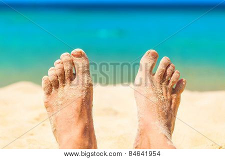 Relaxing on a beach. Feet with the sand.