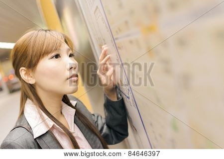 Asian young business woman look at you in front of the station map in the MRT station, shot at Xinyi business district, Taipei, Taiwan.