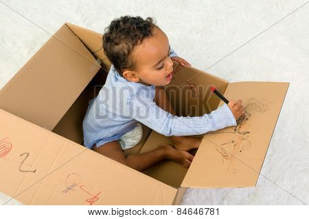 Mixed race little toddler boy sitting in a cardboard box playing with crayons