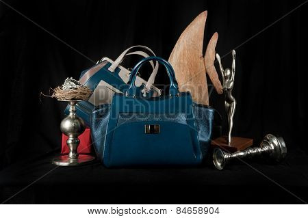 Fashionable handbag  with jewelry and different items for composition on black background.