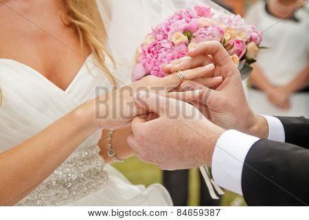 groom putting ring on bride's finger, wedding