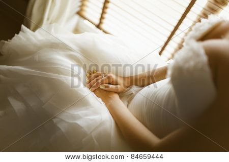 bride's Hand with ring on white dress