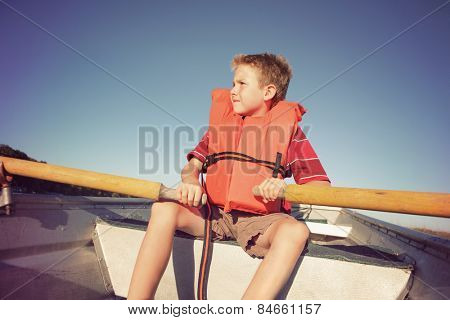 Boy rowing a boat on a lake