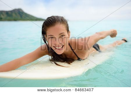 Portrait of surfer woman surfing having fun on Waikiki Beach, Oahu, Hawaii. Female bikini girl laughing on surfboard smiling happy living healthy lifestyle on Hawaiian beach. Asian Caucasian model.