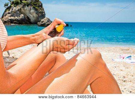 Woman applying suntan lotion from a spray bottle . Greece.