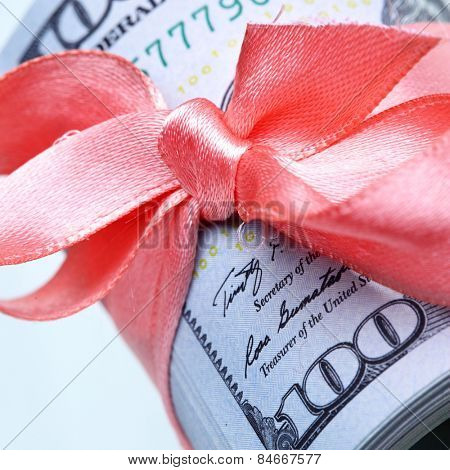 Roll of dollars with ribbon and bow