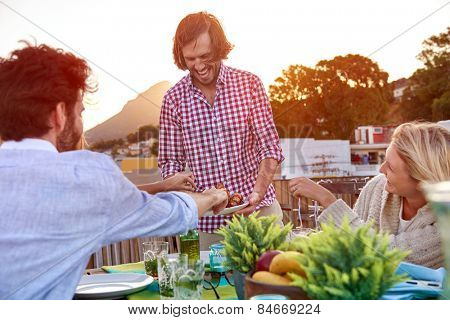 Man serves friends skewer kebabs at outdoor rooftop barbeque dinner party