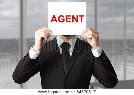 Secret Agent Hiding Face Behind Sign