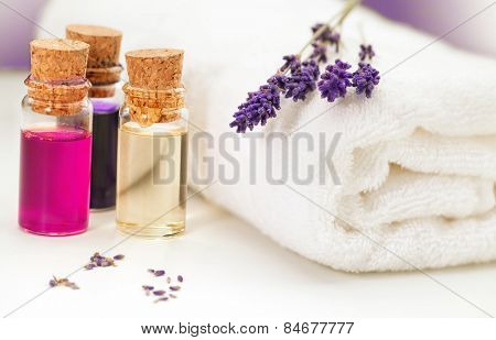 Lavender, towel and oil for massage on white background