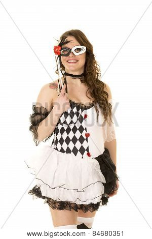 Woman In A Black And White Costume Holding Mask To Face