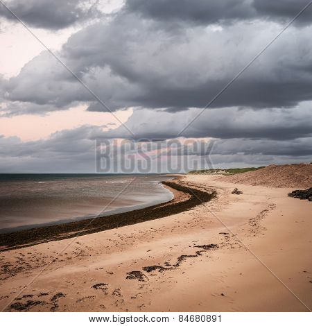 Beach at sunset in Prince Edward Island, Canada with dark cloudy sky, square format