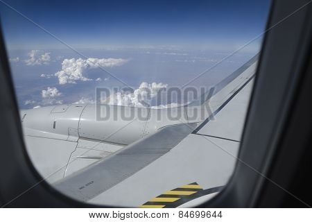 Airplane window with a view of sky and clouds.