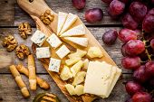 Cheese plate: Emmental Camembert cheese blue cheese bread sticks walnuts grapes on wooden table poster