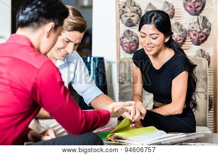 Couple of Caucasian man and Asian woman and shop assistant in furniture store planning furnishing of home together poster