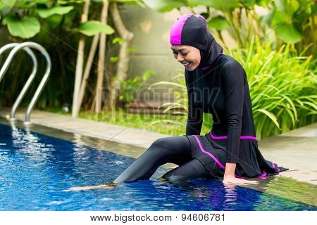Muslim woman or girl sitting at pool in tropical garden wearing Burkini halal swimwear