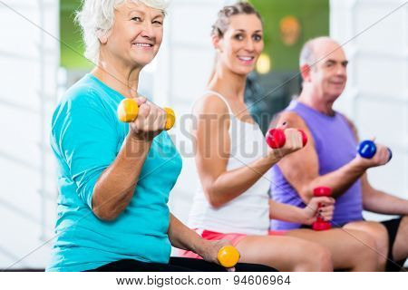 Senior man and women with fitness trainer in gym lifting barbells as sport exercise