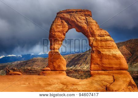 Late evening photo of a Delicate Arch with a dramatic stormy sky in the back. Arches National Park, Utah - USA  poster