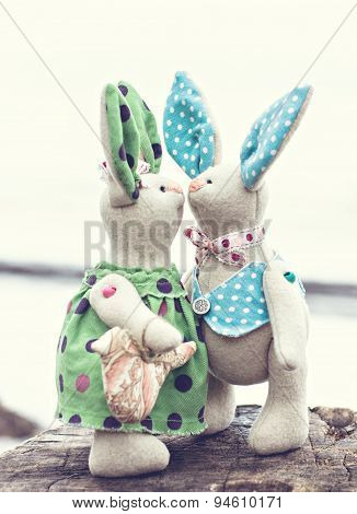 Two toy bunny in love on an old wooden surface. toned photo
