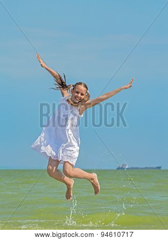 Cheerful Girl  Jumps Over The Sea