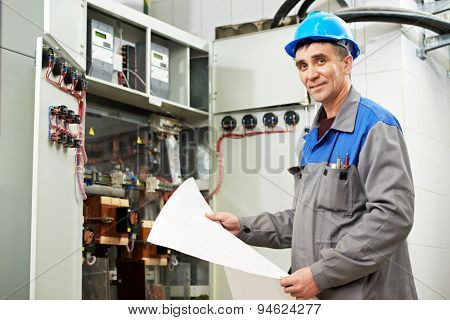 electrician builder engineer inspector with electrical scheme plan near the fuse box