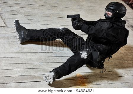 Military industry. Special forces or anti-terrorist police soldier,  private military contractor armed with pistol ready to attack lying on ground during clean-up operation, mission poster