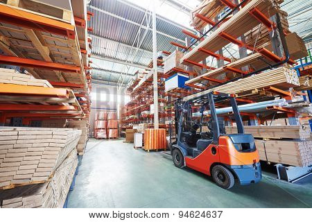 warehouse forklift stacker loader stacking cardboxes in storehouse