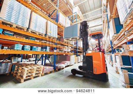 warehouse worker driver in uniform stacking cardboxes by forklift stacker loader