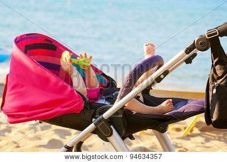 Baby Lying In Stroller On The Beach