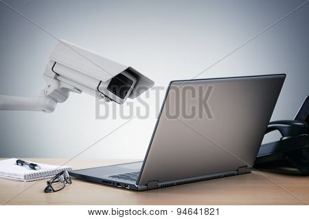 Laptop computer being watched in the office by a security camera concept for big brother surveillance or internet computer security