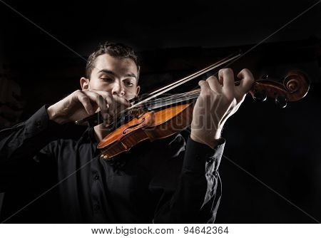 Young man with violin on dark background