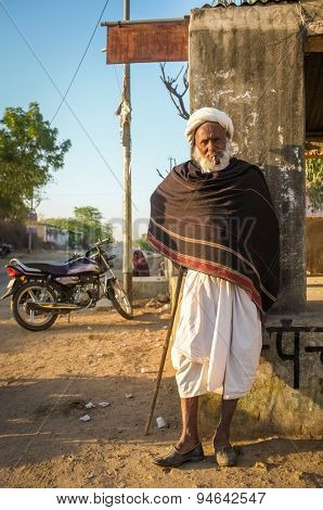 GODWAR REGION, INDIA - 14 FEBRUARY 2015: Elderly tribesman with walking stick, white turban and dark blanket. Rabari or Rewari are an Indian community in the state of Gujarat.