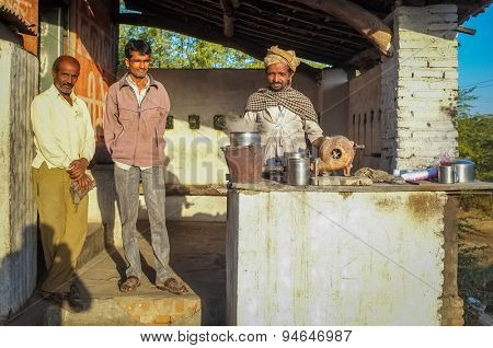 GODWAR REGION, INDIA - 14 FEBRUARY 2015: Man prepares milk tea with traditional wind turbine for making fire. Two customers wait for it to be finished.