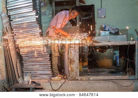 JODHPUR, INDIA - 10 FEBRUARY 2015: Young worker hones metal part and makes sparks.