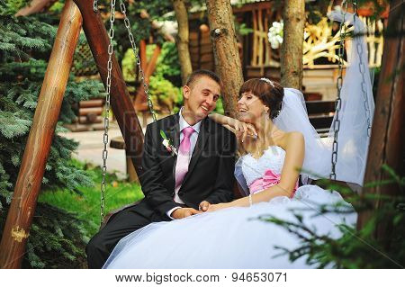Bride And Groom Smile On A Swing On Their Wedding Day