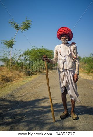 GODWAR REGION, INDIA - 14 FEBRUARY 2015: Elderly Rabari tribesman with big red turban and cane stands on road. Rabari or Rewari are an Indian community in the state of Gujarat.