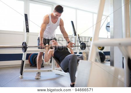 Gym Instructor Supporting Woman In Lifting Barbell