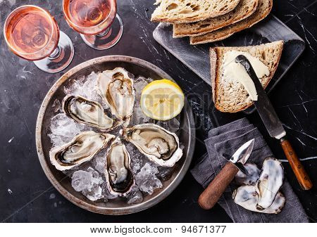 Opened Oysters On Metal Plate With Dark Bread With Butter And Rose Wine On Dark Marble Background