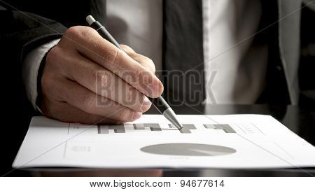 Financial Consultant Reviewing Statistical Graphs And Charts