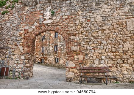 ancient stone wall with entrance gate in the medieval village Rosignano Marittimo Leghorn Tuscany Italy poster