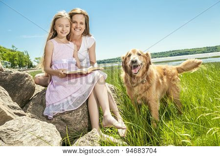 Little girl with mother reading a book in a summer park