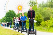Tourist group having guided Segway theme park tour poster