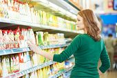 Shopping. Woman choosing bio food cheese products in dairy store or supermarket poster
