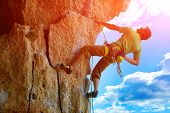 rock climber climbs on a rocky wall poster