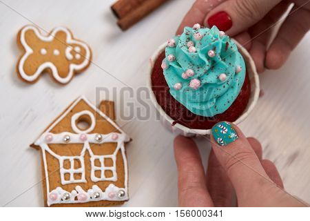 Cupcakes and gingerbreads. Female hand with festive manicure  holding tasty cupcake. 