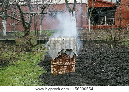 Homemade smokehouse in garden. Winter time. Smoke.