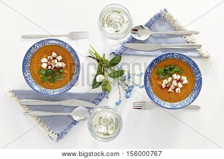 Plates and glasses romantic dinner for two. Homey atmosphere clean white table. Top view. Orange soup